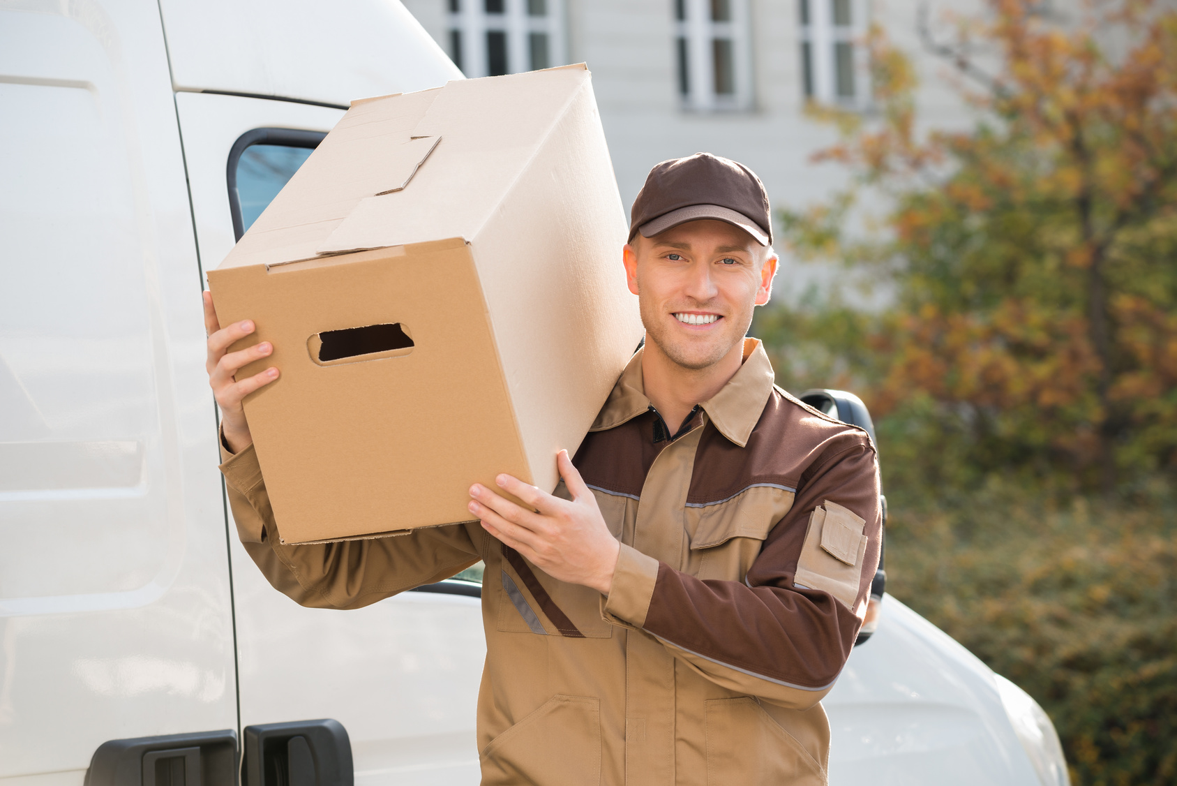 Portrait of young delivery man carrying cardboard box on shoulder with truck in background